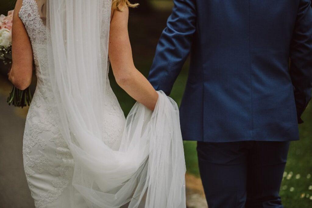Mladoženja u odelu i mlada u venčanici hodaju zajedno