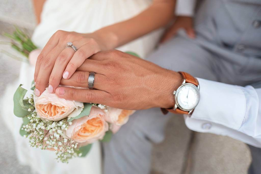 Mlada i mladoženja na dan venčanja sa burmama na rukama